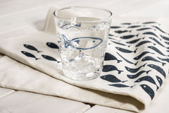 Water-filled Drinking Glass on Table Napkin with Blue Fish Desig Royalty Free Stock Photos