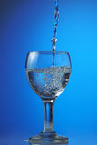Water fills a glass. On a dark blue gradient a background Stock Image