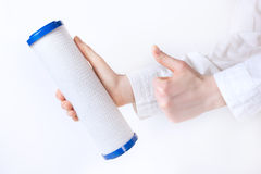Water filter cartridge in human hand. Water filter cartridge in humans two hands Royalty Free Stock Images