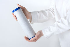 Water filter cartridge in human hands. Water filter cartridge in human hand isolated on white Stock Image