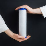 Water filter cartridges in human hands. On black Stock Images