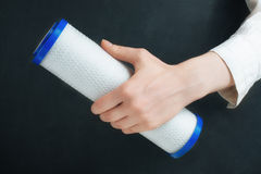 Water filter cartridges in human hands. On black Stock Photos