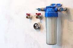 Water filter new installed on a kitchen wall to purify drinking. Water Royalty Free Stock Images