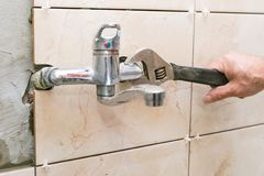 Water fixing - plumber hands with wratch fix tap Stock Photography