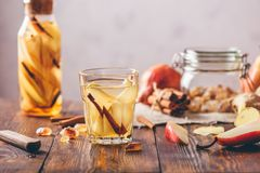 Water Flavored with Pear, Cinnamon, Ginger. Glass of Water Flavored with Sliced Pear, Cinnamon Stick, Ginger Root and Some Sugar. Ingredients on Wooden Table Stock Image