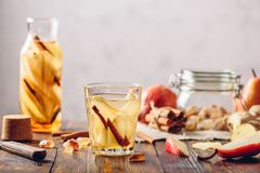 Water Flavored with Pear, Cinnamon, Ginger. Glass of Water Flavored with Sliced Pear, Cinnamon Stick, Ginger Root and Some Sugar. Ingredients on Wooden Table Royalty Free Stock Photos