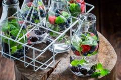 Water in fles met verse bessen Stock Afbeeldingen