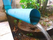 Water Flow from a Blue Pipe stock images