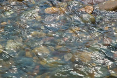 Water flow over multi-colored stones Stock Image