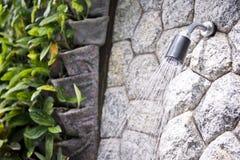 Water flow from shower, outdoor bathroom Stock Image