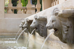 Water flow from statue head of lion in public park in Thailand Royalty Free Stock Photos