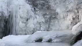 Water flow on waterfall in winter with ice form, close up stock footage