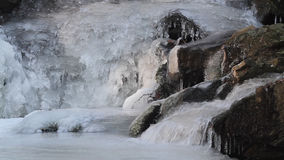 Water flow on waterfall in winter with ice form, close up stock video