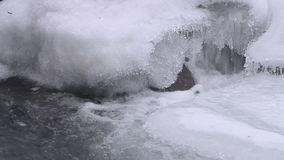 Water flow on waterfall in winter with ice form, close up stock video footage