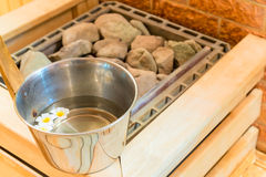 Water with flowers and stones in the sauna Stock Photography