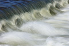 Water flowing. Over a dam edge creating foam Stock Photo
