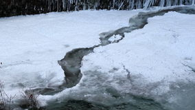 Water Flowing along Frozen Creek in Deep Freeze Winter Portland Oregon 1080p Closeup Royalty Free Stock Image