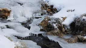 Water flowing down an icy creek. stock video footage