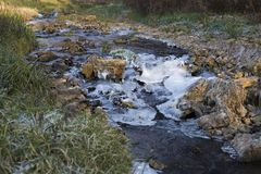 Water flowing down a rocky creek through ice. stock photo