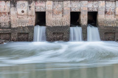 Water flowing from drain to river Stock Image