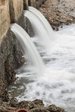 Water flowing from drain to river Royalty Free Stock Photography