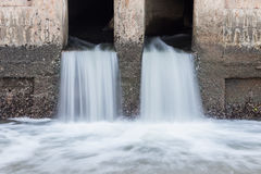 Water flowing from drain to river Royalty Free Stock Photo