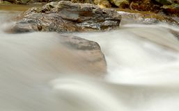 Water flowing fast with stream. Water flowing fast with stream over the rock Royalty Free Stock Photo