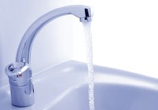Water flowing from the faucet. Against the white background Royalty Free Stock Photo
