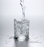 Water flowing into full glass Stock Photos