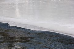 Water flowing through the melting ice surface of the river. Katun River, Altai, Russia Royalty Free Stock Photo