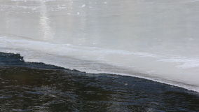 Water flowing through the melting ice surface of the river stock video footage