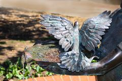 Water flowing from metal bowl with held by hands of statue with metal birds perched with wings outspread. Water flows from a metal bowl with held by hands of Stock Image