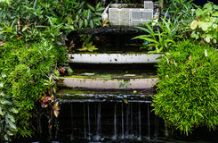 Water flowing off of an artificial waterfall edge with green nat Stock Photos