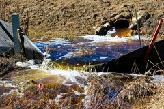 Water flowing out of a culvert in spring.  royalty free stock images