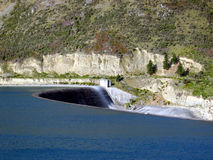 Water flowing over dam. Scenic view of water flowing over power station dam with mountains in background Royalty Free Stock Photos