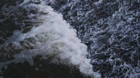 Water flowing through the dam. The water flowing over the dam creates a foamy streams stock video