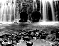 Water Flowing over Dam but None Through the Pipes Stock Photos
