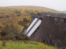 Water flowing over Meldon Dam with wind whipping up spray, Meldon Reservoir, Dartmoor. National Park, Devon, UK Stock Photography