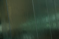 Water flowing over the mirror metal surface. Architectural modern background. Stock Photo