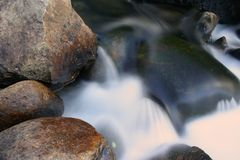 Water flowing over rocks. Background of water flowing over rocks or stones with slow motion blur effect Stock Photos