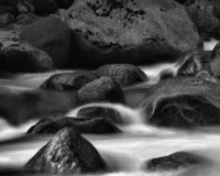 Water flowing over rocks. Black and white photo of water flowing over rocks; motion of water flow is blurry Royalty Free Stock Image