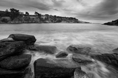 Water flowing over rocks on the beach. Black and white picture of the water of the silky sea flowing over some rocks, with a couple of small houses in the stock photo