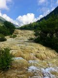 A river flowing over the calcite deposits at Huanglong Scenic Area, China stock photography