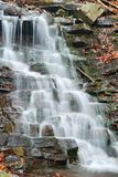 Water flowing over rocks in waterfall cascade Royalty Free Stock Images