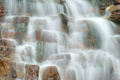 Water flowing over rocks in waterfall cascade Stock Photo