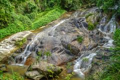 Water Flowing Over Rocky Slope. Tropical Waterfall in Thailand.  stock photography