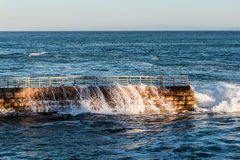 Water Flowing Over Seawall at La Jolla Children's Pool Royalty Free Stock Photography