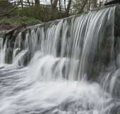 Water flowing over a small waterfall Royalty Free Stock Images