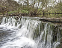Water flowing over a small waterfall Royalty Free Stock Photos