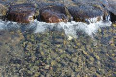 Water flowing over the stepping stones. Water flowing over rounded stepping stones in a river Stock Photo